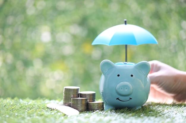 Bescherming, spaarvarken met hand die de paraplu en stapel muntgeld op natuurlijke groene achtergrond houdt, financiënverzekering en veilig investeringsconcept