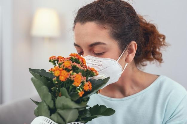 Bescherming tegen allergenen. jong meisje met paardenstaart geniet van bloemengeur terwijl ze een wit persoonlijk beschermend ademhalingsmasker draagt