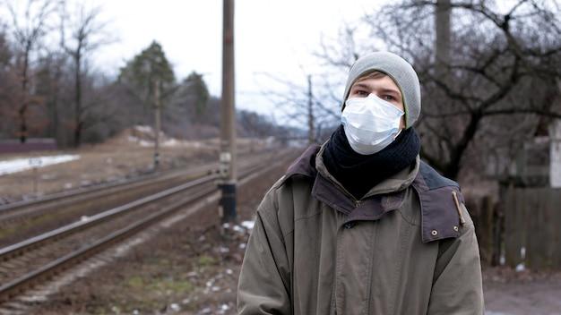 Bescherming tegen griep in de samenleving, een man in een medisch masker, wacht op een trein.