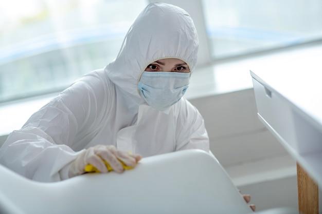 Bescherming tegen virussen. persoon in beschermende werkkleding die huisdesinfectie maakt