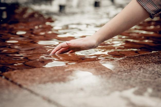 Bescherming van zoet water op aarde. uitdroging. close-up vinger raakt water en waterdruppel aan en creëert natuurlijke en kalme golven, kalm concept.