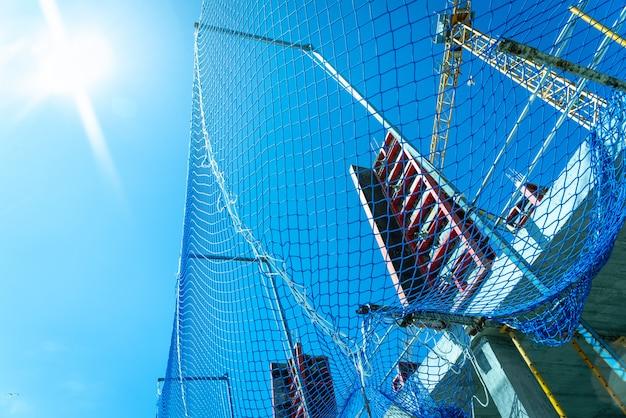 Beschermingsnet in een metselwerkwerkplek in de bouw van de pijlers van een gebouw