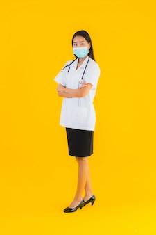 Beschermt de portret mooie jonge aziatische artsenvrouw met masker voor covid19