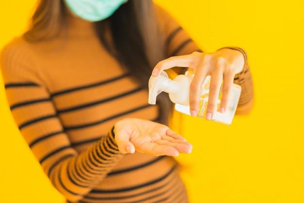 Beschermt de portret mooie jonge aziatische vrouw met de nevel van de maskeralcohol en gelfles in haar hand voor tegen coronavirus of covid19