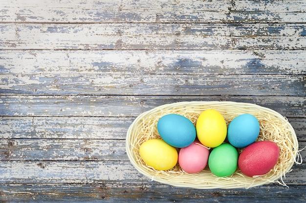 Beschilderde eieren in een mand op een houten achtergrond.