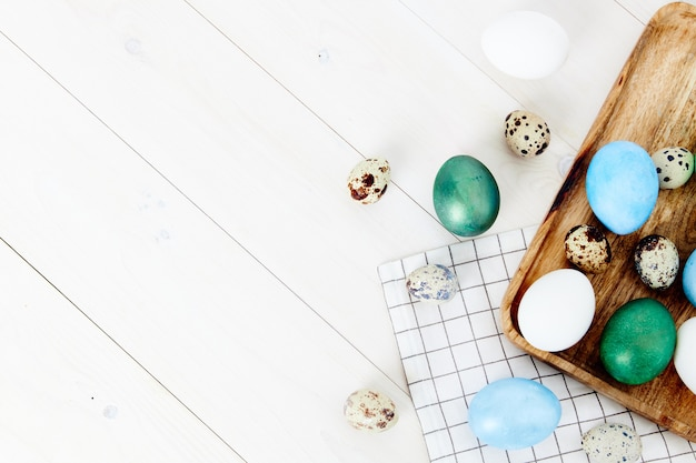 Beschilderde eieren op een houten bord en geruite stof paasvakantie tradities