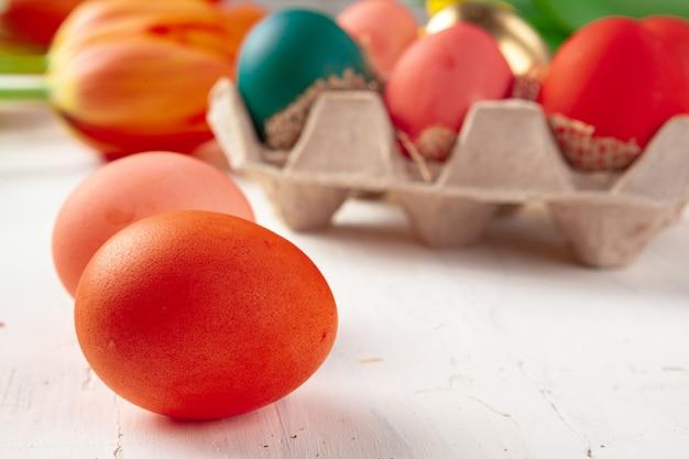 Beschilderde paaseieren in een eggbox met verse tulpen