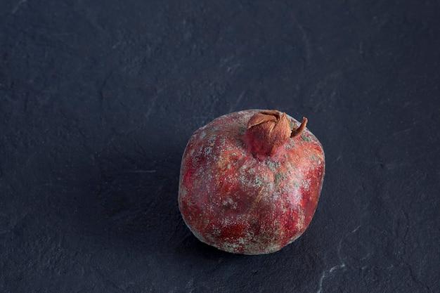 Beschimmeld granaatappelfruit op een donkere achtergrond ruimte kopiëren
