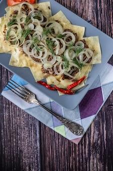Beshbarmak is een nationale tataarse schotel, vierkante pasta met gekookt vlees en uien.