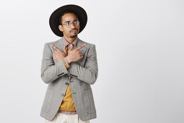 Besluiteloos afro-amerikaanse man die besluit, op zoek naar de rechterbovenhoek dacht tijdens het kiezen, zijwaarts wijzend