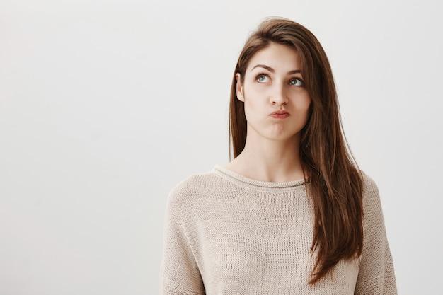 Besluiteloos, bedachtzaam meisje neemt een besluit en kijkt aarzelend linksboven