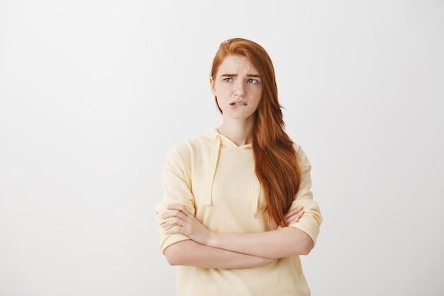 Besluiteloos bezorgd roodharige meisje bijt op lip en kijkt bezorgd naar links