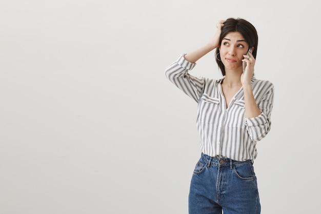 Besluiteloos dom meisje krabt hoofd onzeker, praat aan de telefoon, maakt keuze en kijkt linksboven