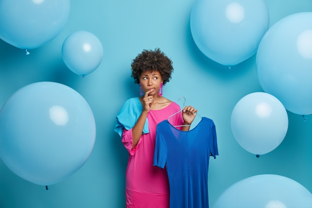 Besluiteloos doordachte afro-amerikaanse vrouw kiest outfit voor banket, denkt wat te dragen, houdt jurk op hangers, geïsoleerd over blauwe muur met grote ballonnen. vrouwen, mode, kleding