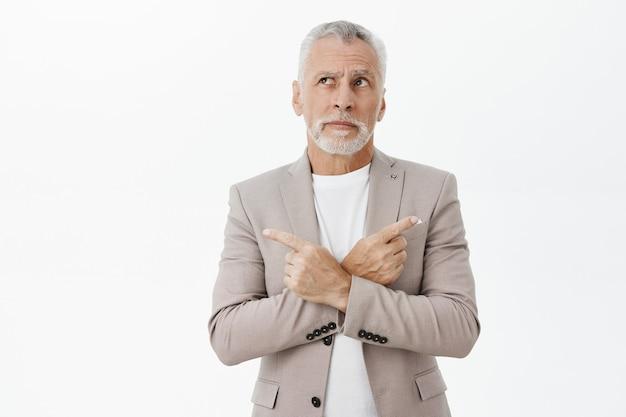 Besluiteloos doordachte volwassen zakenman zijwaarts wijzend en op zoek linkerbovenhoek, keuze maken, beslissen