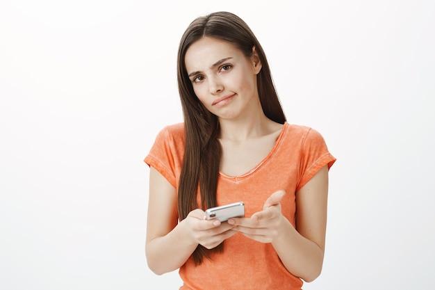 Besluiteloos en onzeker schattig brunette meisje schouderophalend tijdens het gebruik van smarpthone, grijns onzeker