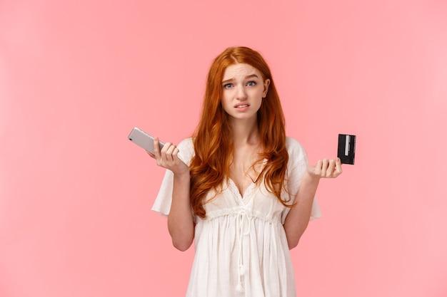 Besluiteloos en onzeker schattige europese roodharige vrouw die haar schouders ophaalt, verwarde en nutteloze camera kijkt, schouderophalend met smartphone en creditcard in handen, weet niet welke online bestelling