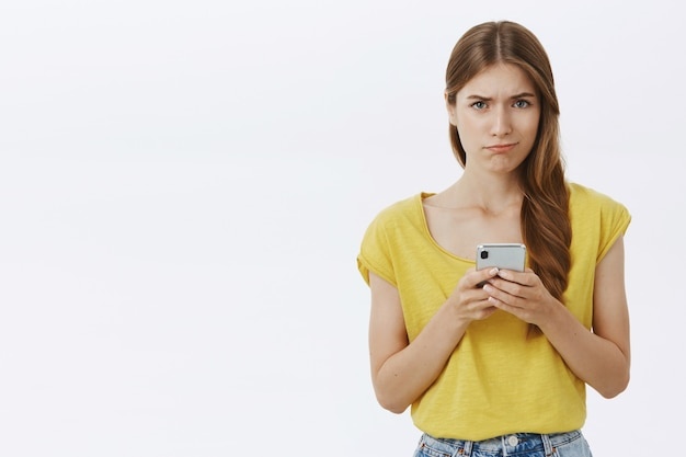 Besluiteloos en somber verdrietig meisje kijkt boos, smartphone vast te houden
