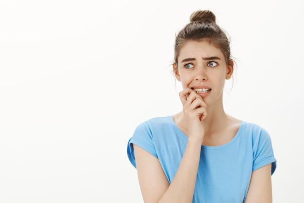 Besluiteloos en verbaasd jonge vrouw vingernagel bijt en wegkijken onrustig, bezorgd en verward