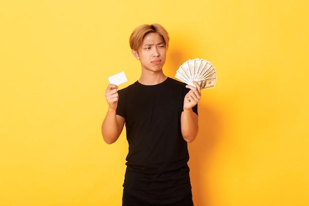 Besluiteloos en verward jonge aziatische man kijkt verbaasd naar geld terwijl hij contant geld en creditcard vasthoudt