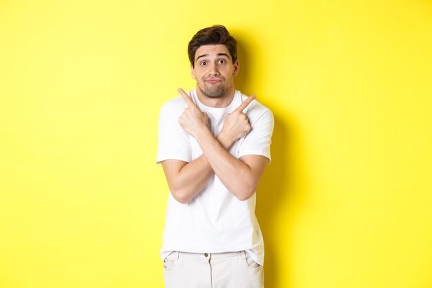 Besluiteloos man wijzende vingers zijwaarts, worstelende om een beslissing te nemen, advies te vragen, staande op gele achtergrond.