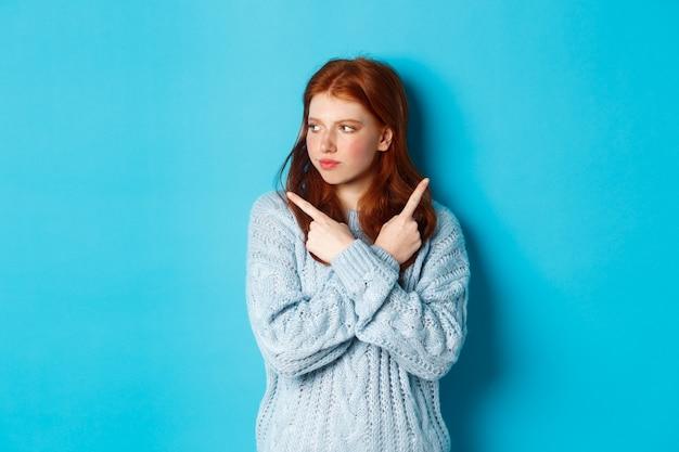 Besluiteloos roodharige tienermeisje dat een beslissing neemt, de vingers zijwaarts wijst en twijfelachtig naar links kijkt, staande in een trui tegen een blauwe achtergrond