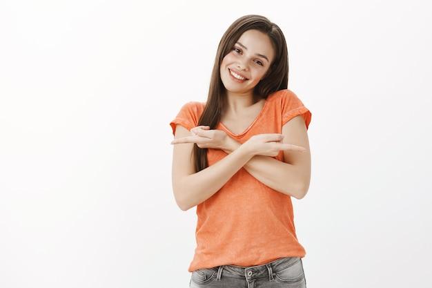 Besluiteloos schattig en mooi meisje wijzende vingers zijwaarts, richtinggevend, demonstreren twee varianten
