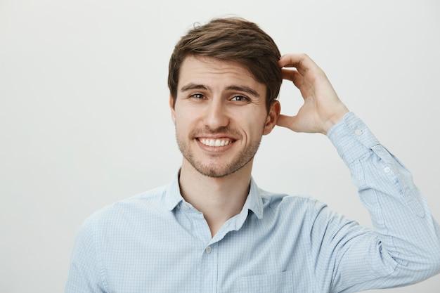 Besluiteloos schattige kerel lachend en scarch hoofd, geen idee