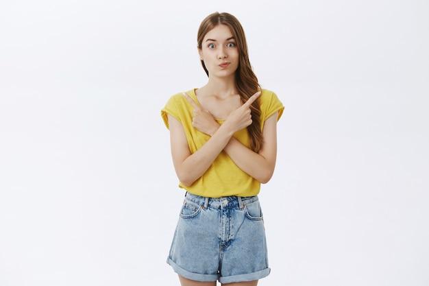 Besluiteloos verbaasd schattig meisje wijst zijwaarts en wijst twee varianten, keuze maken