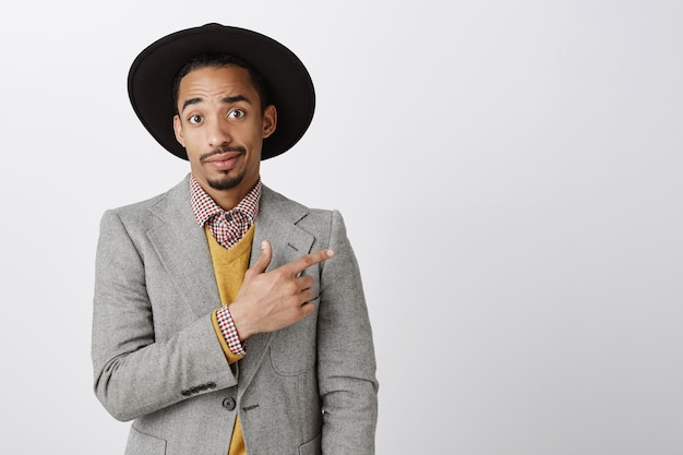 Besluiteloze afro-amerikaanse zakenman in pak wijst rechter bovenhoek, twijfelachtig op zoek
