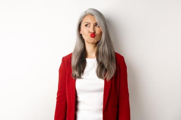 Besluiteloze aziatische zakenvrouw tuit lippen en kijkt nadenkend in de linkerbovenhoek, staande op een witte achtergrond.