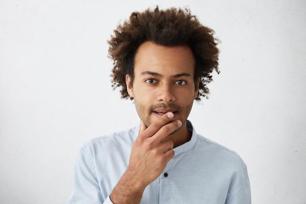 Besluiteloze bedachtzame student met een donkere huidskleur en stoppels die de lippen met de vingers aanraken