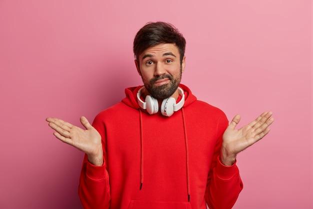 Besluiteloze duizendjarige man met baard, haalt zijn schouders op, steekt handpalmen omhoog, gekleed in rood sweatshirt, gebruikt stereokoptelefoon, grijnst problematisch, begrijpt niets, poseert over roze pastelkleurige muur