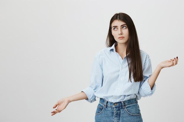 Besluiteloze schattige vrouw die haar schouders ophaalt, aarzelt over de keuze