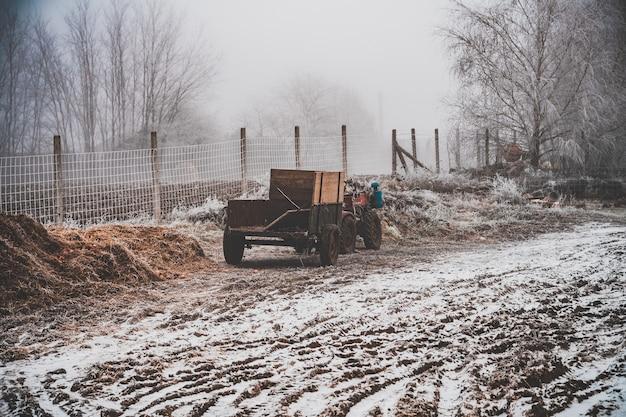 Besneeuwd veld met een wagen vastgemaakt aan een motorfiets met vier wielen