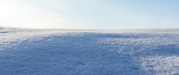 Besneeuwde achtergrond, besneeuwd oppervlak met een duidelijk uitgedrukte textuur van sneeuw in de ochtendzon en heldere zonnige hemel