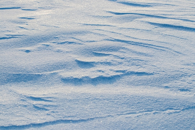 Besneeuwde achtergrond, besneeuwde oppervlakte van de aarde na een sneeuwstorm in de ochtend in het zonlicht met verschillende lagen sneeuw