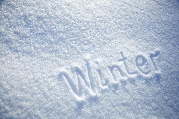 Besneeuwde achtergrond met inscriptie winter op besneeuwde achtergrond