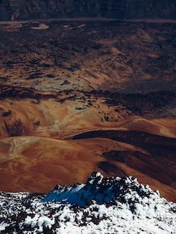 Besneeuwde berg in de buurt van droge heuvels