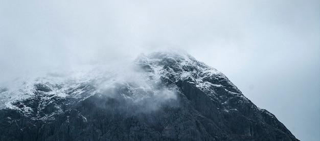 Besneeuwde berg op een mistige dag