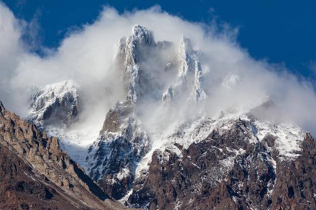 Besneeuwde bergtop in wolken