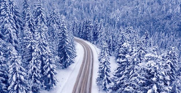 Besneeuwde bergweg en bos, drone uitzicht. besneeuwde bergweg en bos, drone uitzicht. prachtig winterlandschap.