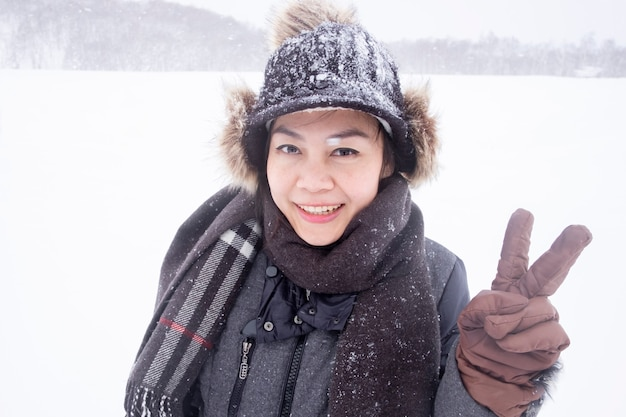 Besneeuwde dag in de winter gelukkig aziatische vrouw slijtage trui twee v-teken groet symbool in een skigebied, gelukkig reizen overzee concept