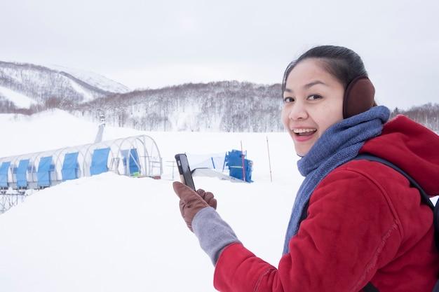 Besneeuwde dag in de winter gelukkige aziatische vrouw draag een rode trui met een smartphone in een skiresort, gelukkig reisconcept overzee