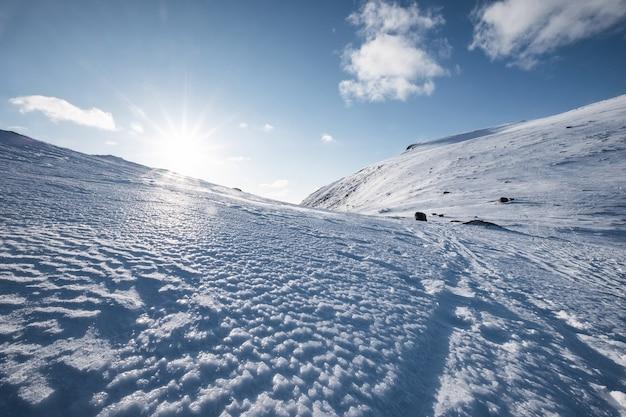 Besneeuwde heuvel met zonlicht en blauwe lucht op de winter op de lofoten-eilanden