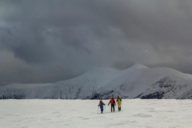 Besneeuwde karpatische bergheuvels met verre wandelaars