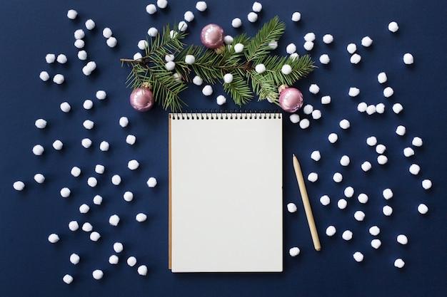 Besneeuwde kerst achtergrond met blanco papier notebook en decoraties