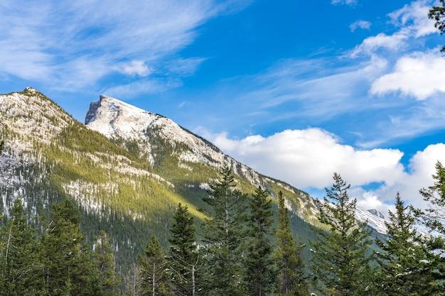 Besneeuwde mount rundle-bergketen met besneeuwd bos over blauwe lucht en witte wolken in de winter