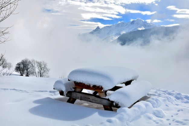 Besneeuwde picknicktafel in natuurlijk landschap