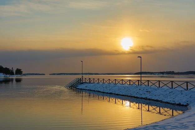 Besneeuwde pier bij zonsondergang aan zee
